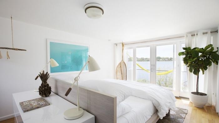 design intérieur style minimaliste, modèle de chambre à coucher blanche au parquet bois avec accessoires de decoration marine