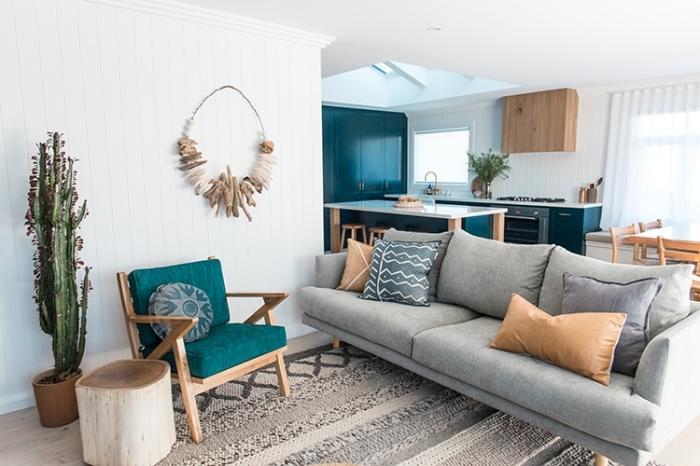 exemple de salon minimaliste avec objets d'esprit marin, meuble bois avec housse vert marine, suspension diy en bois flotté