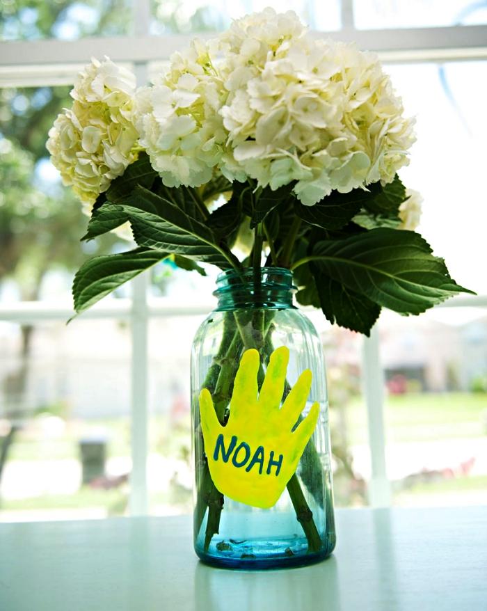 idée de cadeau fête des mères à fabriquer avec les tout petits, empreinte de main en peinture gonflante pour décorer une fenêtre ou un vase en verre