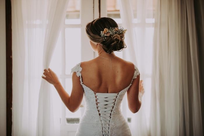 idée de coiffure cheveux attachés pour mariage, exemple de chignon flou bas avec serre-tête florale et boucles