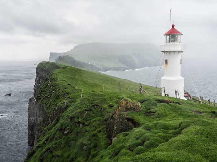 Les iles Faroe, islande paysage, la beauté de la terre, les plus beaux paysages du monde, phare sur un colin vert entouré de l'océan et un grand lac