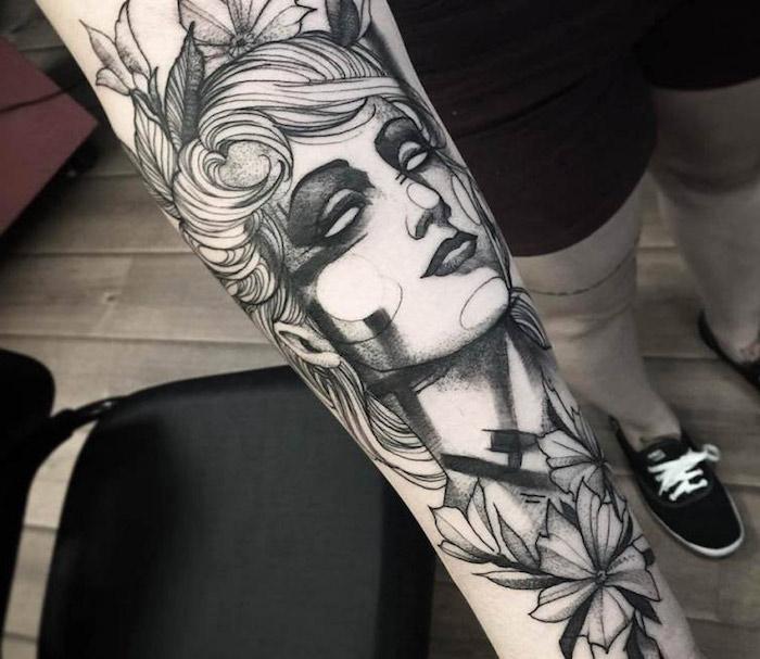 tatouage avant bras homme avec une femme tatouée, tête de femme entourée de fleurs