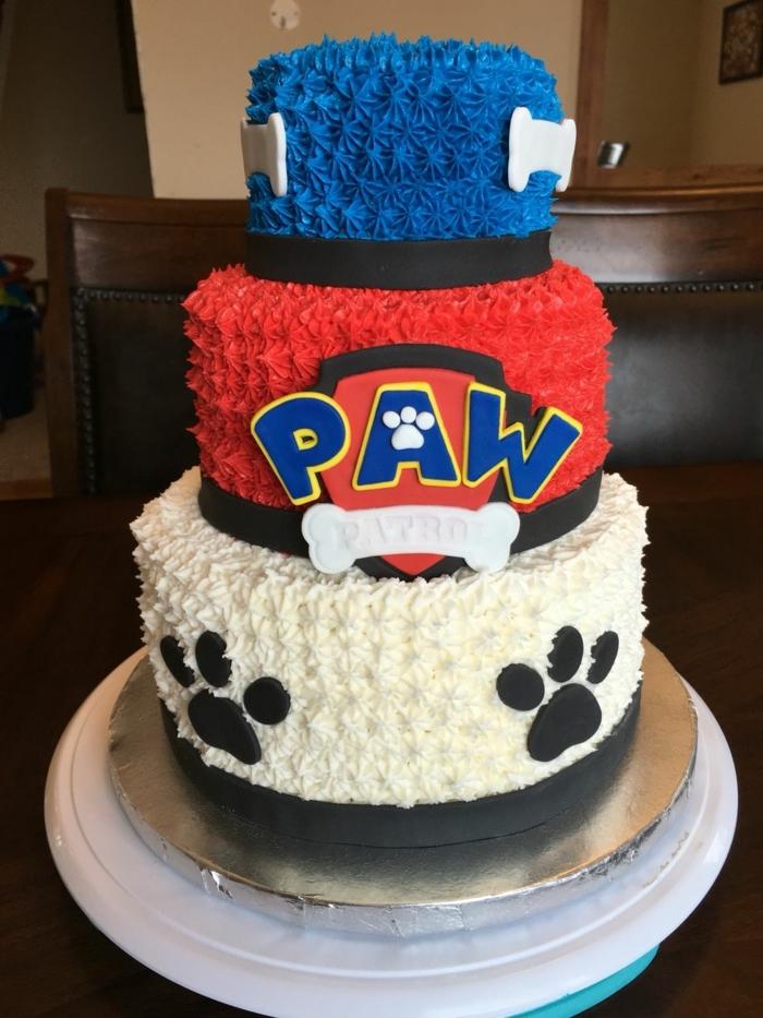 joli gâteau de trois étages, gâteau anniversaire pat patrouille, gateau bleu, blanc et rouge; pattes de chien
