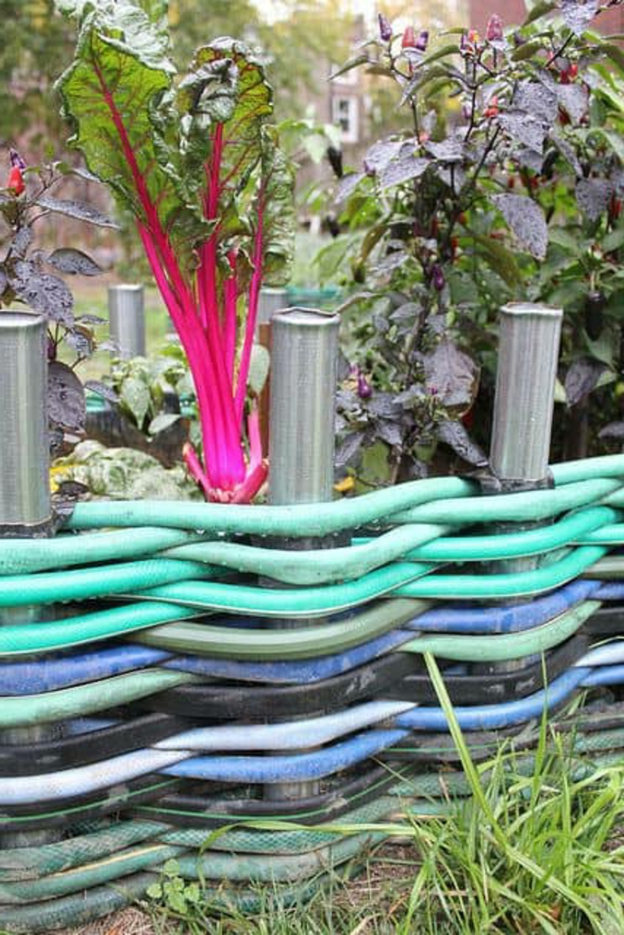 vieux tuyaux d'arrosage tressés multicolores, bordure de massif créative, plate-bande légumes