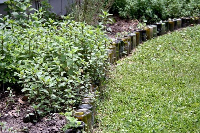 pelouse verte, bordure de massif en bouteilles multicolors, parterre de jardin à bricoler