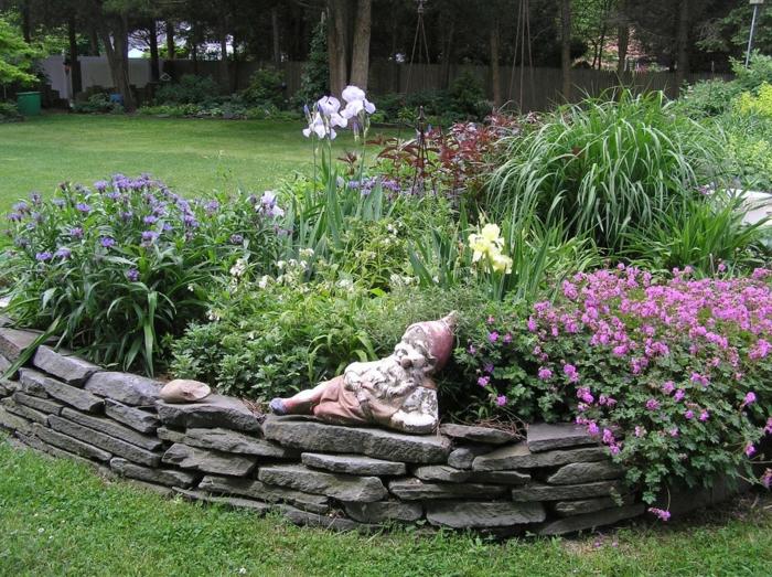 aménagement extérieur, massif de fleurs délimité avec pierres, statue elf, jardin et arbres