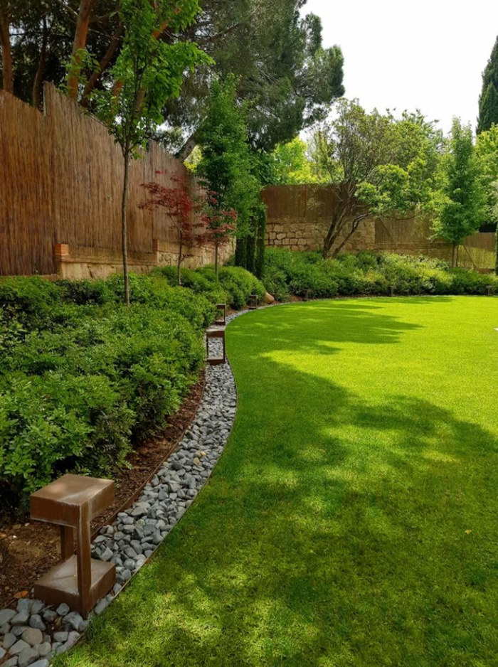 gazon bient entretenu, haie bambou, buissons plantés, jardin spacieux et vert déco minime