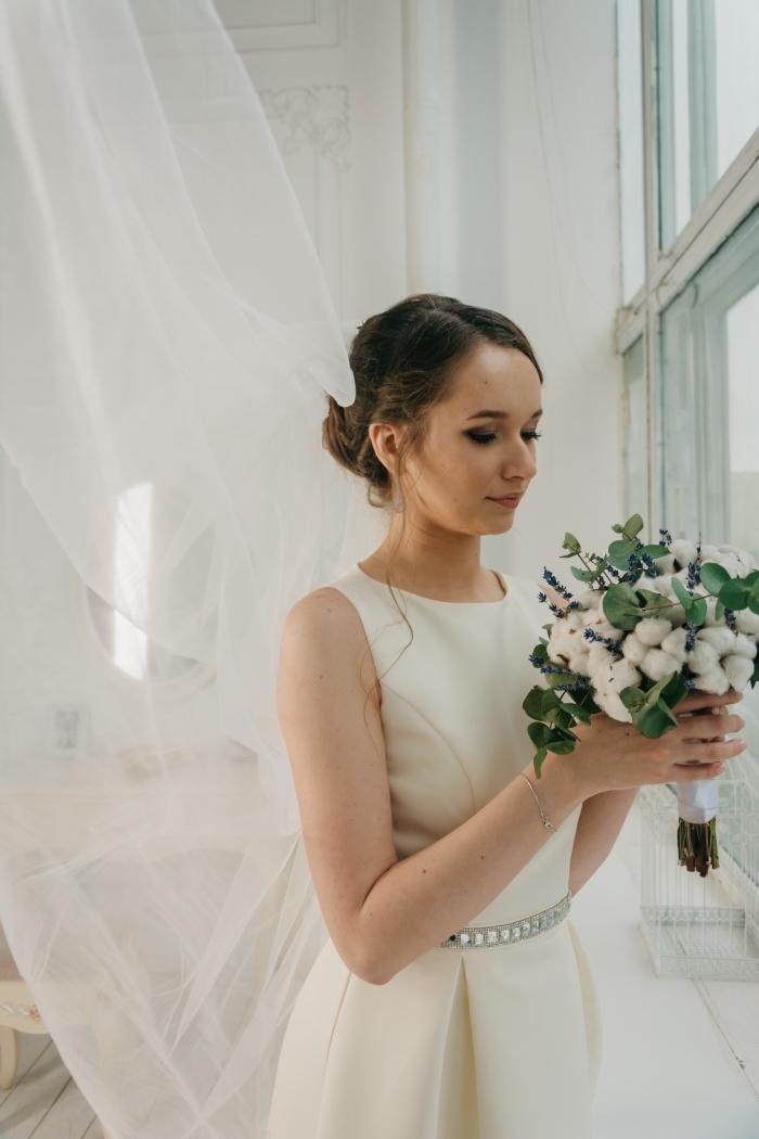 modèle de robe de mariée courte et fluide, exemple de coiffure cheveux attachés en chignon bas fluide avec mèches