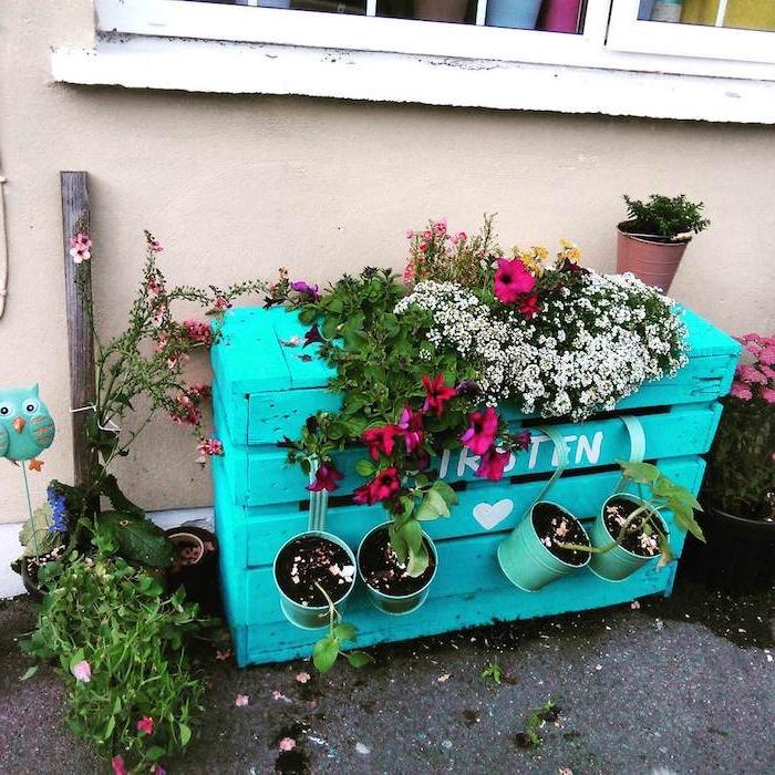 rangements pour fleurs en palette de bois repeinte en bleu, plantes grimpantes et pots de fleurs accrochés