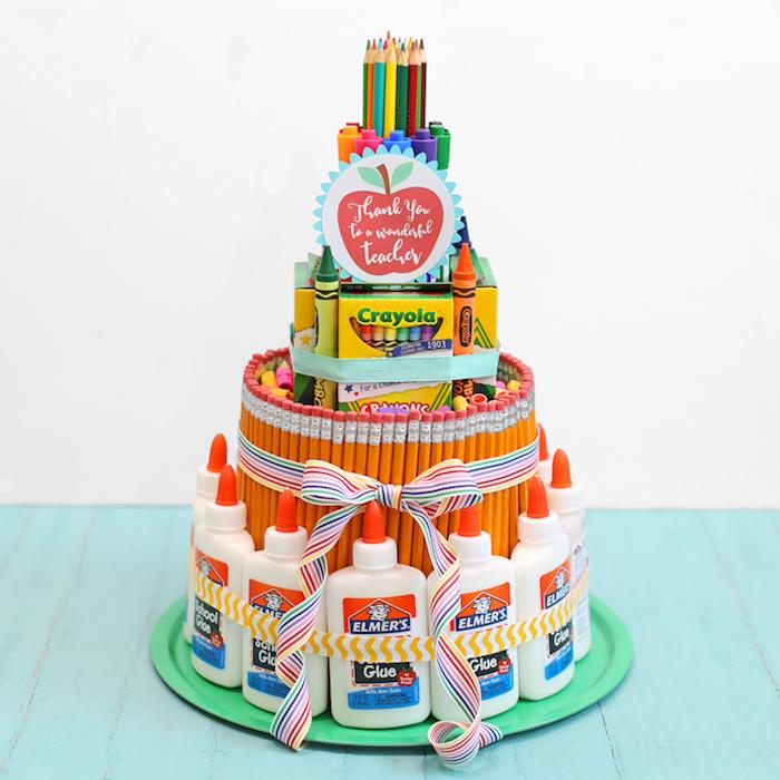 gateau de fournitures scolaires, cadeau fin d annee maitresse origina composé de crayons, crayons en couleurs, feutres, craies de cire, bouteilles de colle