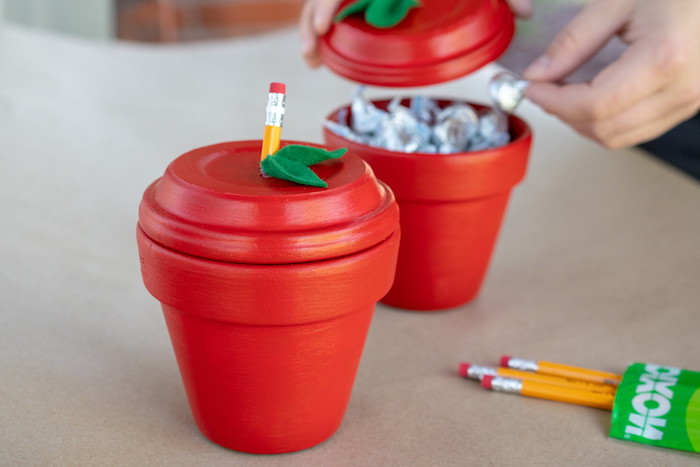pot de terre cuite repeint de peinture rouge avec des bonbons à l intérieur, cadeau maitresse maternelle original