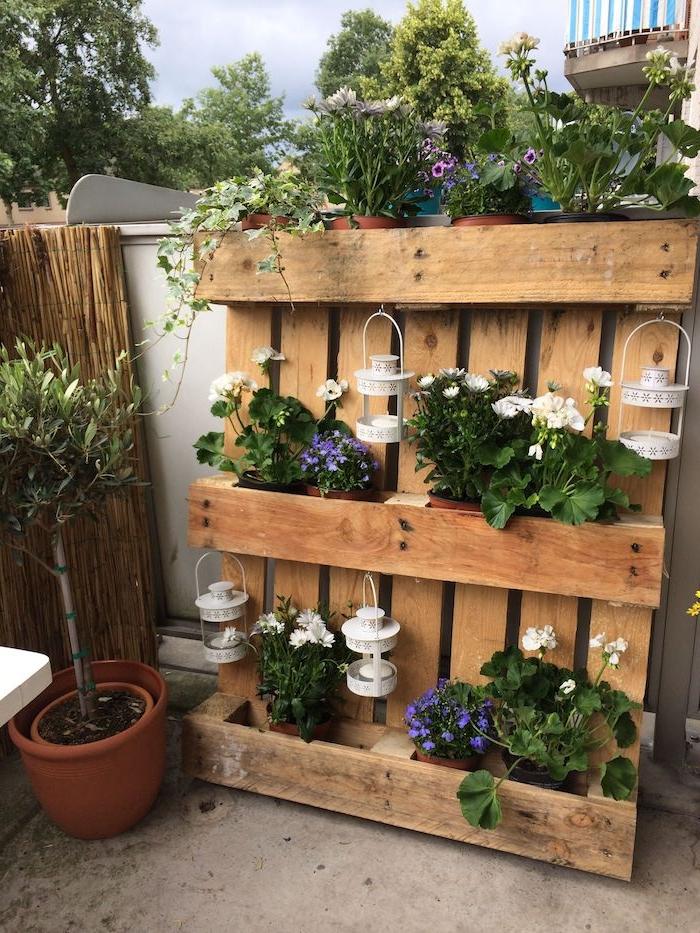 idée de jardin vertical à plusieurs pots de fleurs rangés sur une palette décomposée et des lanternes blanches