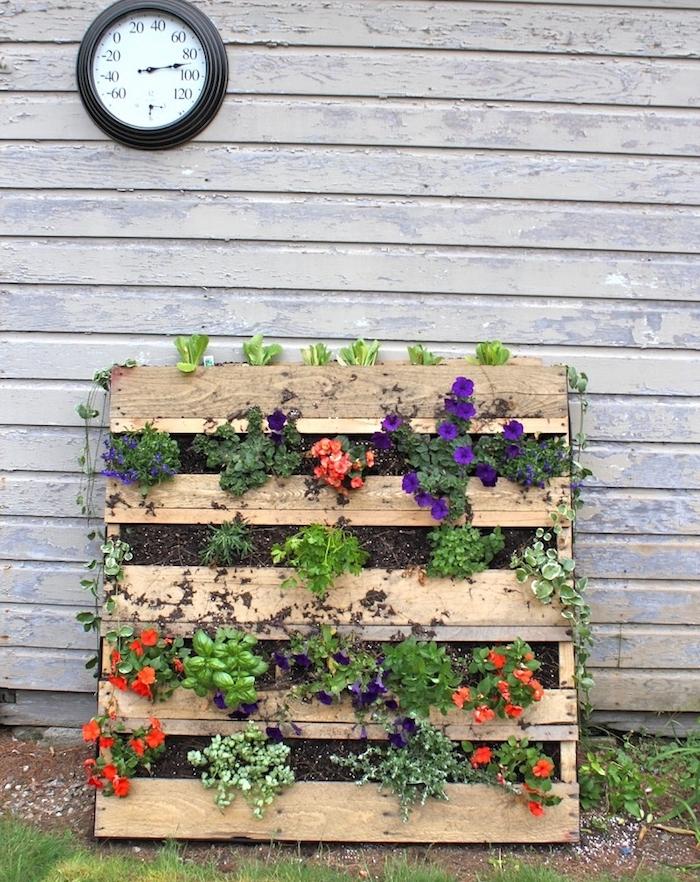 idée de mur végétal palette avec des fleurs plantées dans terreau situé dans les interstices d une palette