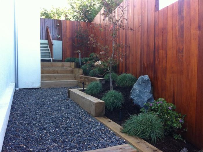 aménagement extérieur contemporain, escalier en traverses de bois, buissons, grande pierre décorative