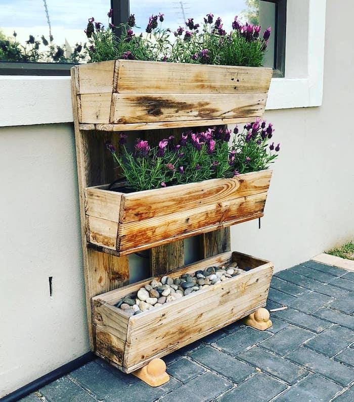 bac à fleurs diy à trois niveaux en bois recyclé et planches de bois assemblées avec galets, fleurs, amenagement exterieur