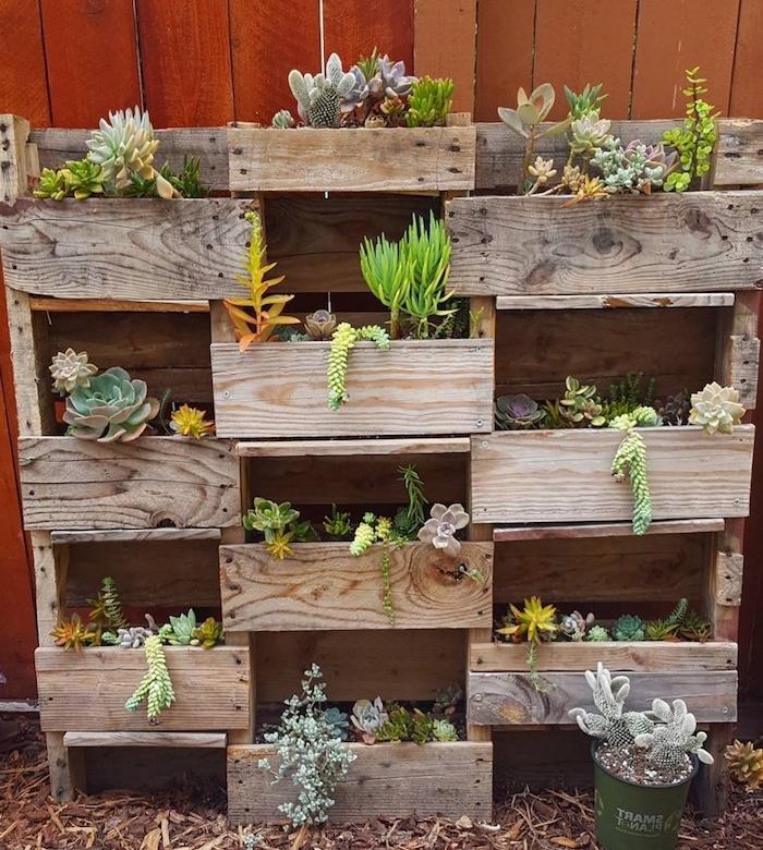 plusieurs bacs à fleurs en bois assemblés dans un rangement plantes exterieur adossé à un mur de cloture en bois