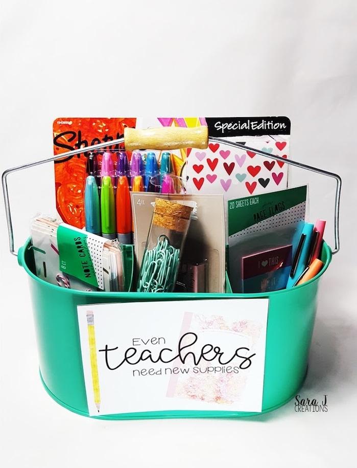 fournitures de bureau dans un panier en metal vert rempli de stylos, feutres, agenda, étiquettes et trombones