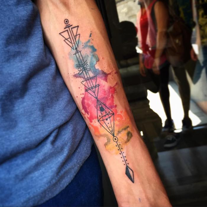 tatouages avec symboles originaux sur fond en aquarelle, nuages colorés abstraits