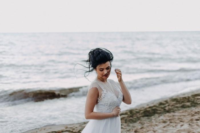 exemple de chignon haut flou tressé avec mèches tombantes, idée de chignon cheveux long, modèle robe mariage avec dentelle florale