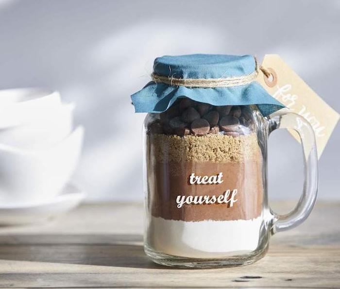 gros verre rempli de mélange pour faire des brownies maison avec couvercle en tissu bleu, cacao, pépites de chocolat, sucre