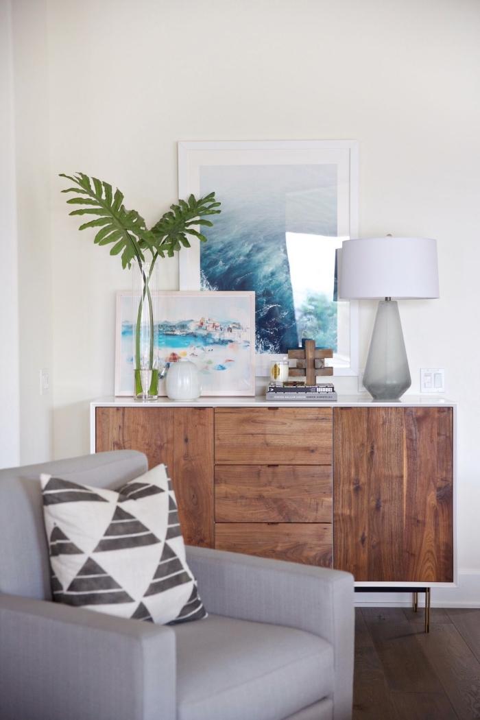exemple de décoration style bord de mer avec photos océaniques, pièce beige aménagée avec meubles bois foncé et canapé gris