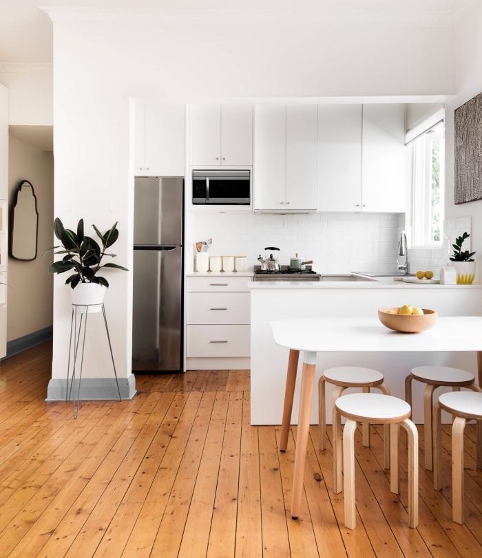 modèle de cuisine équipée pas cher, décoration cuisine ouverte blanche avec plancher en bois et équipement inox