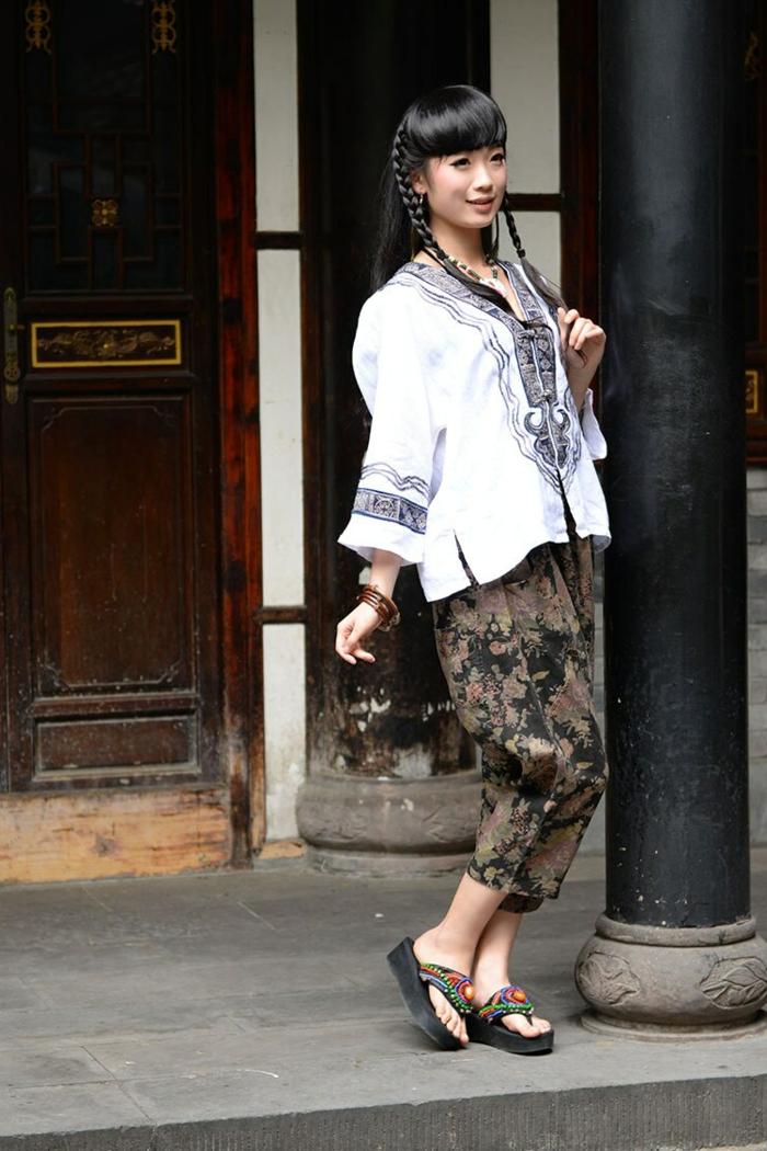 pantalon motifs végétaux, chemise blanche avec broderies, coiffure en tresses, femme style hippie
