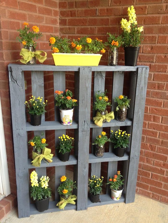 palette de bois recyclée et repeinte en gris, avec des étagères de rangement à plusieurs pots de fleurs