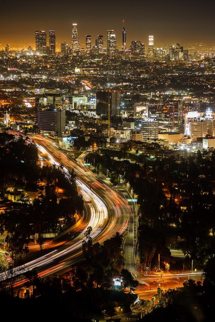 Los Angeles en nuit, belle photo avec les lumières de la nuit des bâtiments et voitures, LA traffic et précautions écologiques