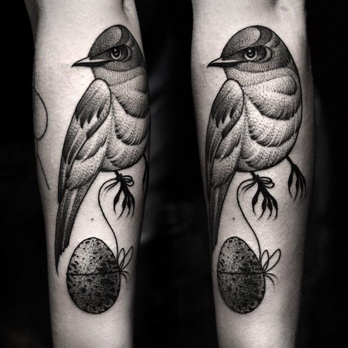 oeuf accroché au bout d un fil et oiseau gris graphique sur le bras, modele design de tatouage animalier