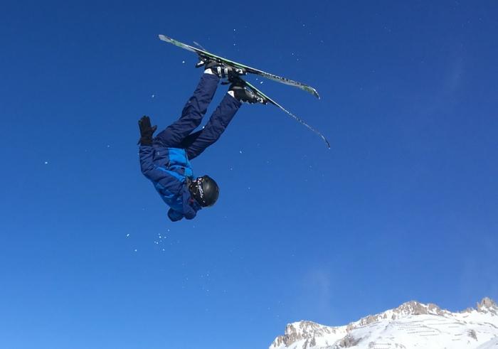 figure de skieurs en l'aire, skier en France, montagne enneigée et ciel bleu, trouver une destination de vacances en France