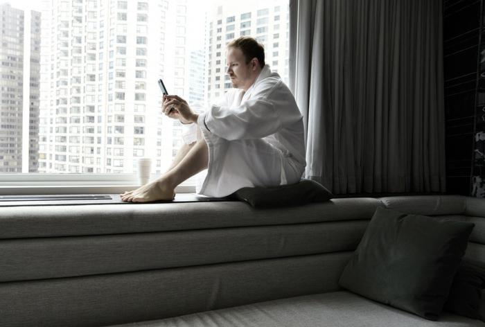 un homme assis près de la fenêtre avec son téléphone, meuble gris, rideaux gris