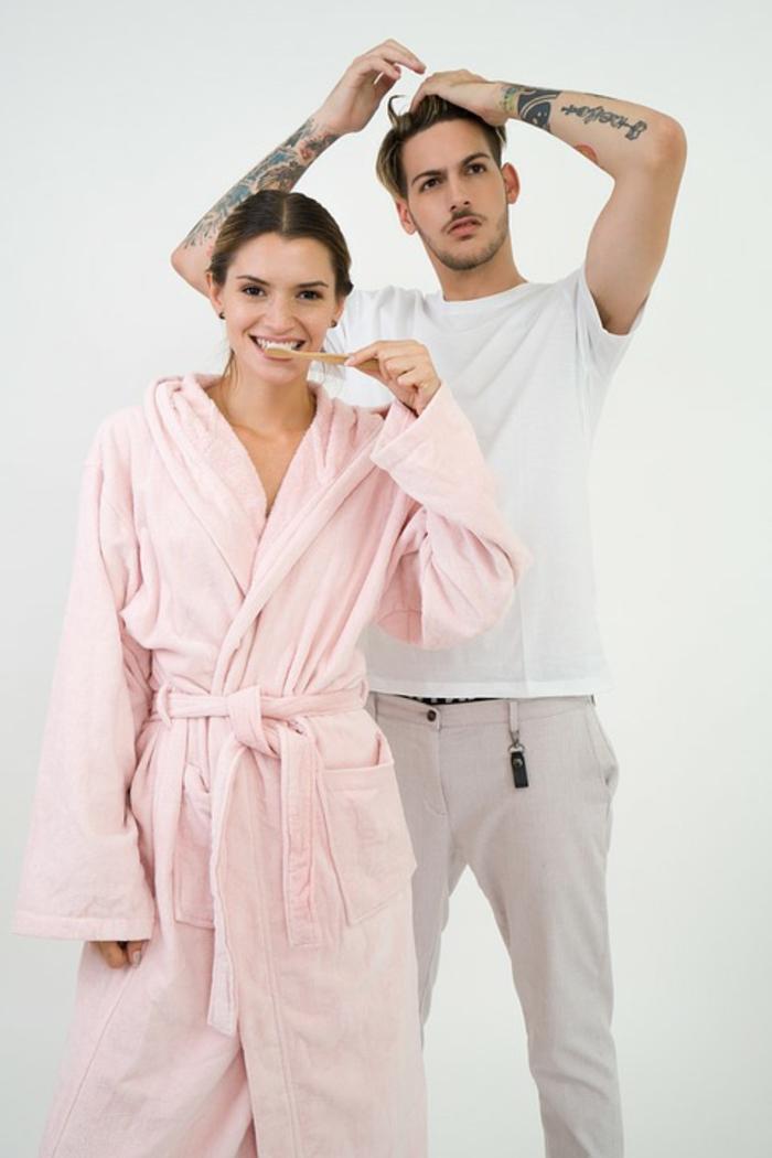jeune couple, femme en peignoir rose, col chale, homme avec t-shirt blanc, tatouaes bras et pantalon été beige