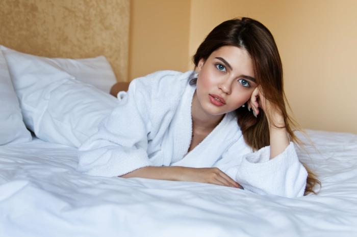 jeune femme en peignoir de bain blanc dans son lit, linge de lit blanc, linge de bain moderne