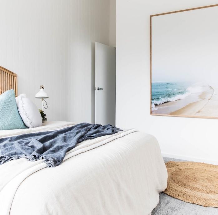 design intérieur style marine dans une chambre à coucher blanche aménagée avec meubles bois, idée art murale avec peinture paysage marine
