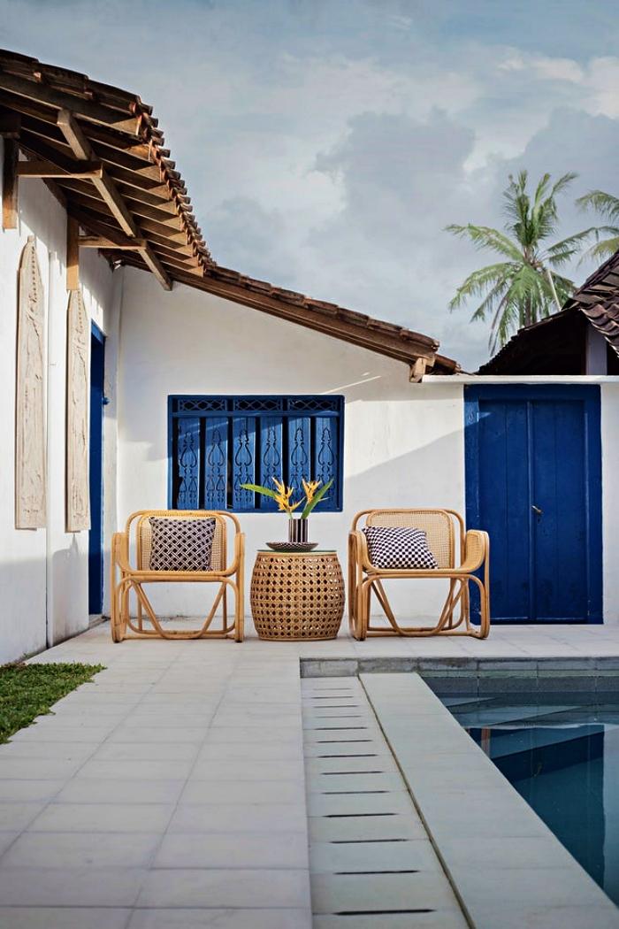 aménagement d'un petit coin détente autour de la piscine avec petite table basse et deux chaises en bois