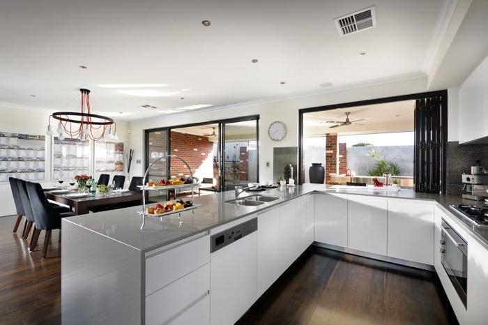 cuisine en u avec bar, modèle de cuisine aménagée en trois murs, déco de cuisine blanc et gris au parquet bois foncé