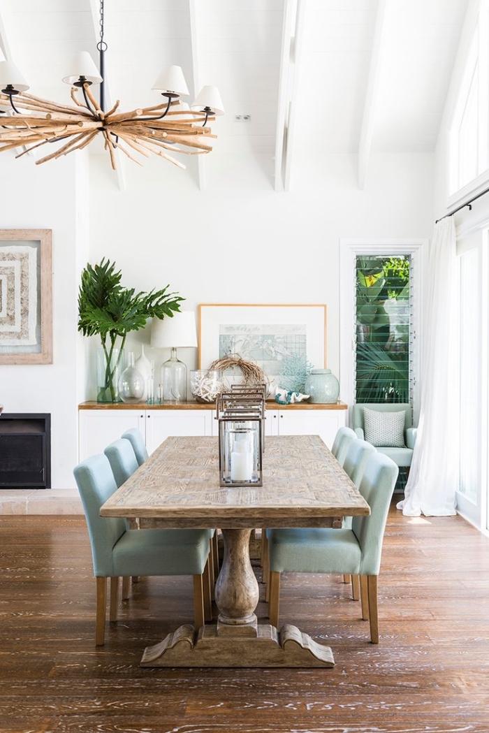 salle à manger blanche avec plancher bois foncé, modèle de suspension luminaire en bois flotté, pièce à deco mer