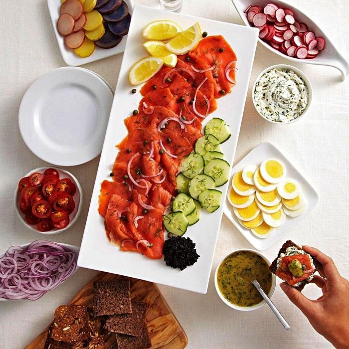plateau avec tranches de saumon fumé, concombre, citron et légules pour composer son toast apero, des sandwiches apéro décomposés