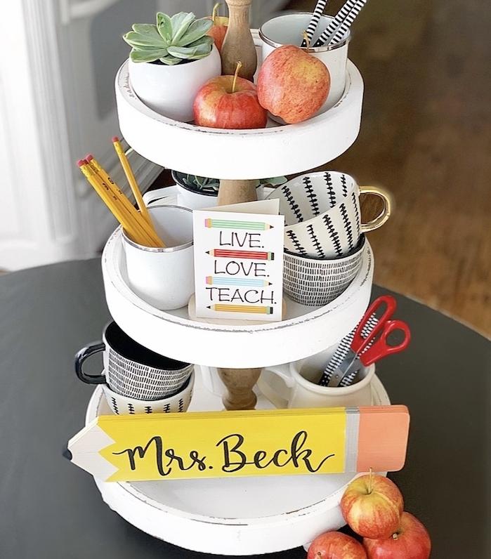 plateau de service à trois niveaux avec des tasses à thé, des pommes, ciseaux, crayons, pot de succulent, cadeau maitresse personnalisé