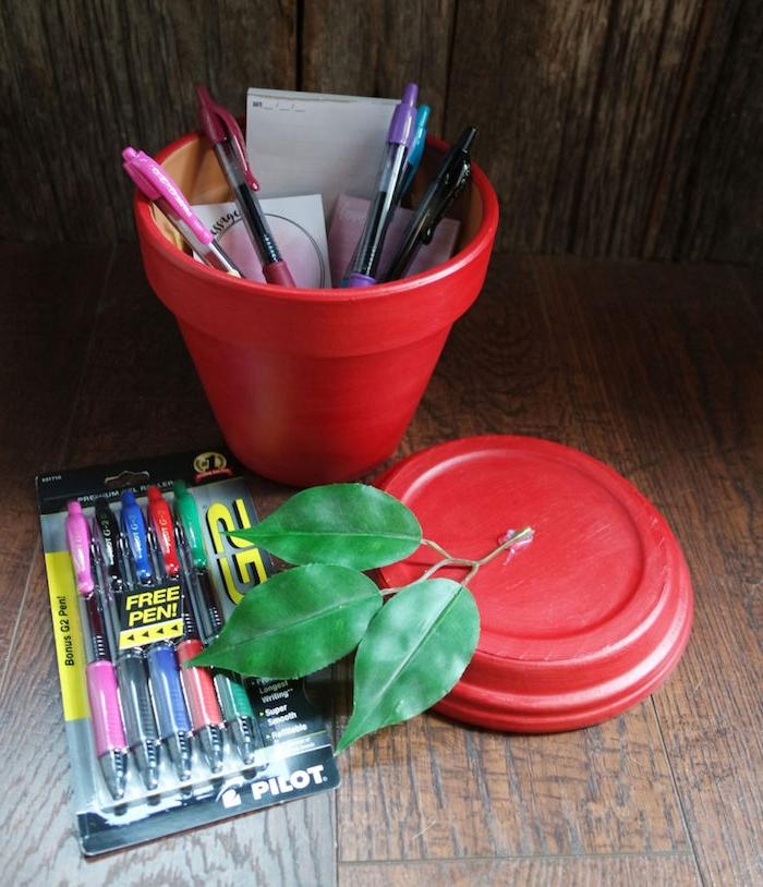 cadeau merci maitresse, idee de pot de fleur repeint en rouge avec motif pomme et branche de feuilles vertes en top, stylos à l intérieur d un pot