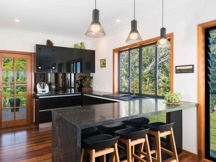 modèle de cuisine blanche et noire avec accents en bois foncé, idée aménagement cuisine en forme de U ouverte