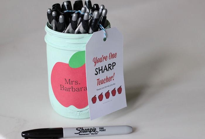 pot à crayons repeint en bleu clair avec motif pomme appliqué en dessus et plusieurs stylos à l intérieur, étiquette cadeau original