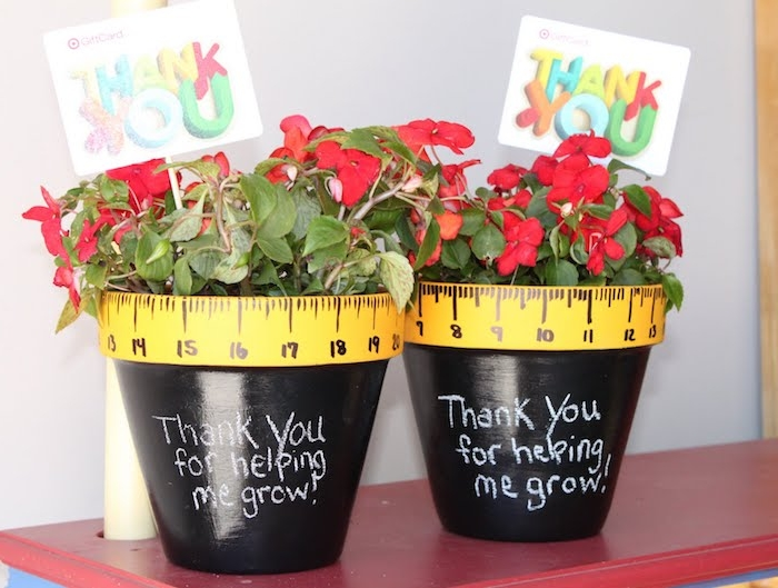 pot de fleur repeint de peinture noire avec écriture lettres à la craie et un rebord à motif règle dessiné avec fleur rouge à l intérieur