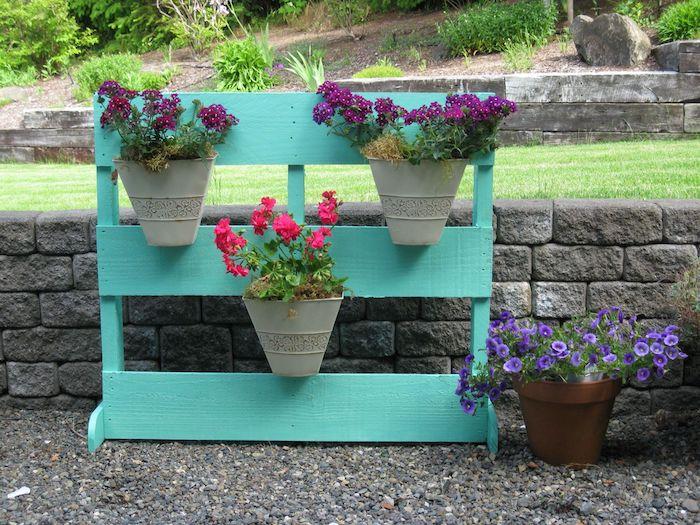 pots de fleurs fixés sur un rangement pour plantes en lattes de bois repeintes de couleur bleue