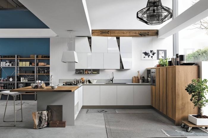 agencement cuisine moderne aux murs blancs avec accents en bois brut, déco cuisine ouverte vers un salon avec mur bleu