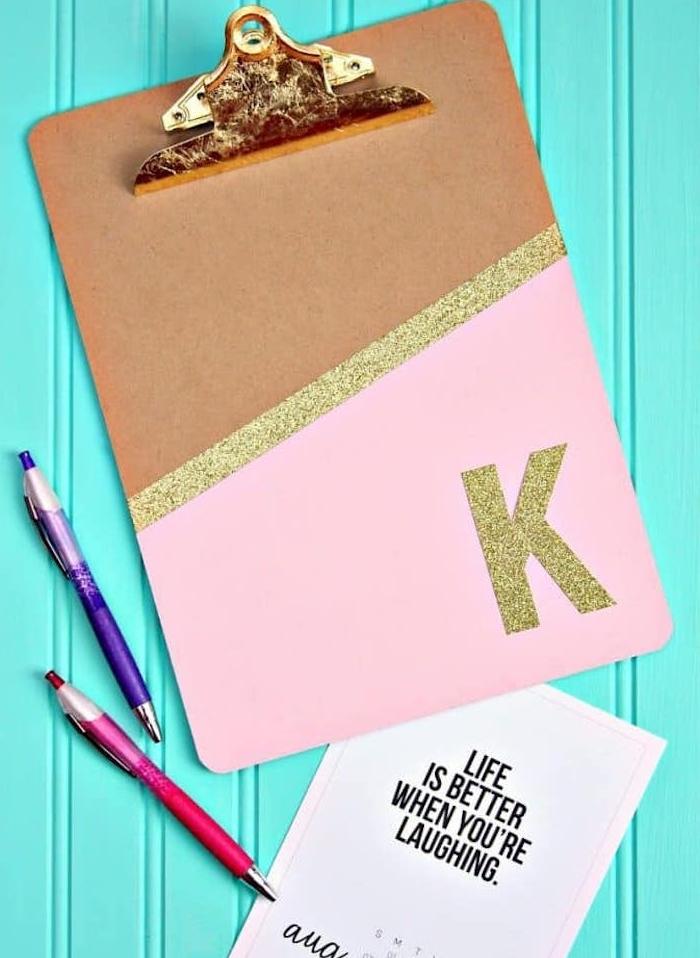 porte bloc décoré à peinture rose et une lignes dorée pailletée et la lettre K en paillettes dorées, cadeau maitresse personnalisé
