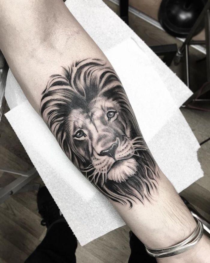 tatouage lion za al figure graphique et des yeux verts sur bras, dessin symbole de la force et la sagesse