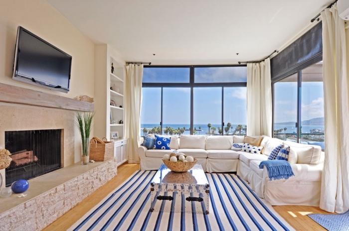 idée maison bord de mer, modèle de salon aux murs beige et plafond blanc aménagé avec grand canapé d'angle