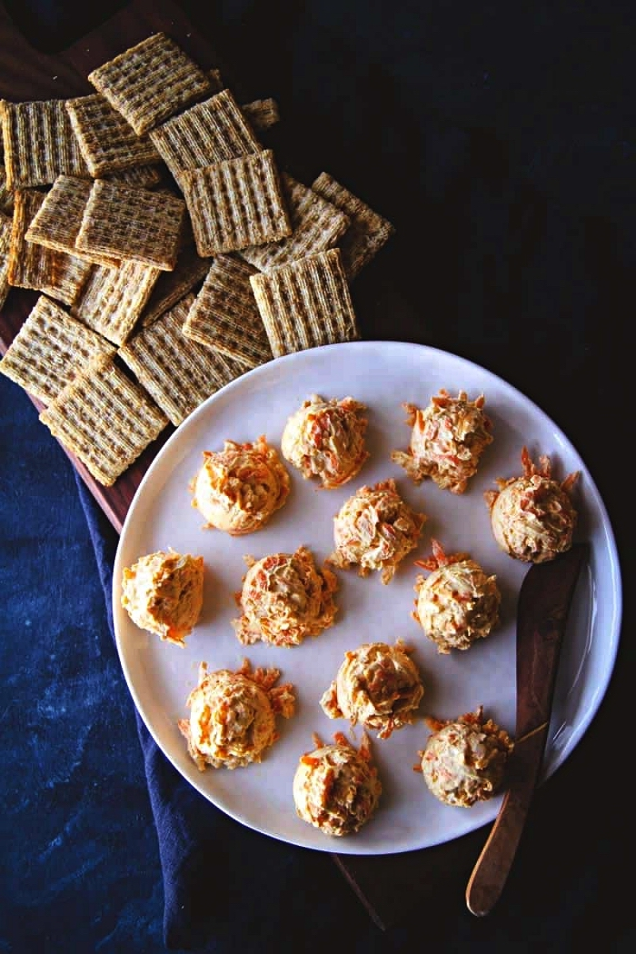 amuse bouche facile sans cuisson, recette de billes de fromage à la crème et de carottes râpées servies avec des crackers salés